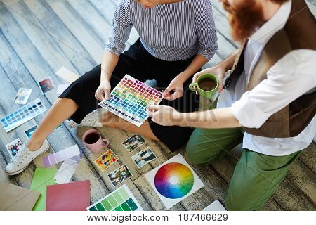 Team of creative designers discussing project, choosing color scheme laying out swatches on wooden floor