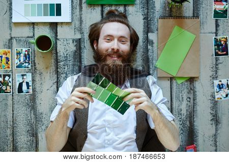 Directly above view of smiling creative designer lying on wooden floor working in modern studio and choosing color scheme from palettes