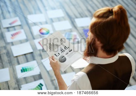 Back view portrait of young creative designer  working on color concept and scheme laying out swatches on floor and reading plan documentation