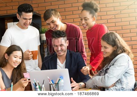 Group of casual interracial people looking at laptop computer discsussing work - brainstorming and teamwork concepts