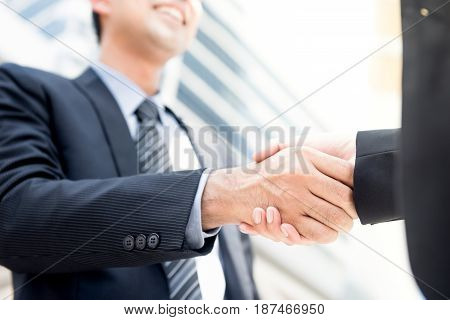 Businessman making handshake with a businesswoman - greeting dealing merger and acquisition concepts