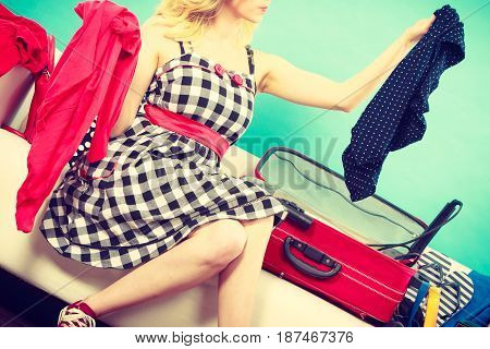 Woman Choosing Things To Pack Into Suitcase