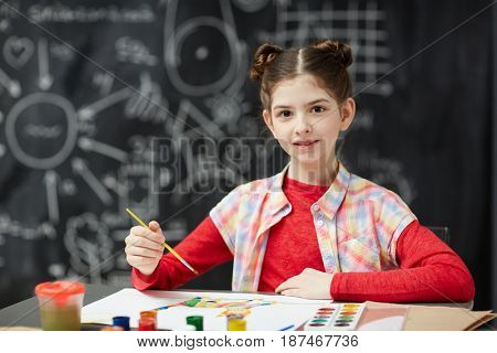 Portrait of pretty little girl  painting pictures in art class looking at camera sitting  against blackboard