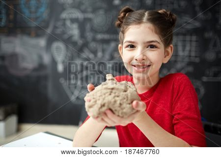 Portrait of cute little girl looking at camera and smiling  while playing with kinetic sand in child development center