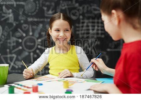 Portrait of cute smiling little girl painting pictures with friend in art studio class sitting against blackboard