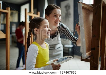 Portrait of happy little girl enjoying painting class in art studio, with young teacher helping her
