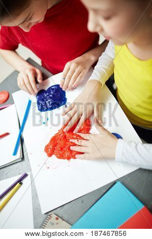 High angle portrait of two little girls plying with playdough during art class, enjoying feeling it with fingers, developing fine motor skills