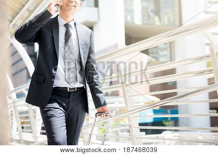Businessman calling on cell phone while pulling baggage and walking in outdoor covered walkway