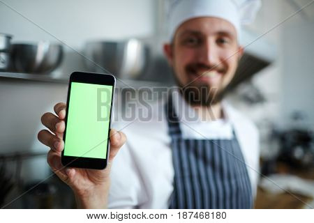 Pastry-chef showing something in smartphone
