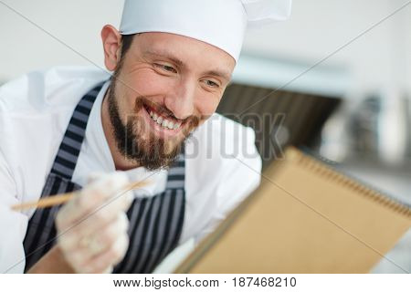 Staff of bakery-shop with notepad writing list of bread assortment