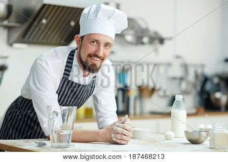 Chef of bakery-shop leaning at workplace
