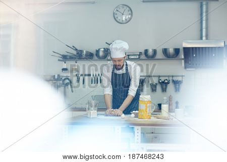 Baker in uniform kneading dough at workplace