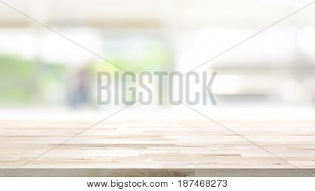 Wood table top on blur kitchen window background 16:9 proportion - can be used for display or montage your products (or foods)