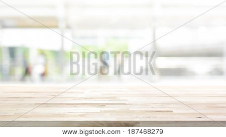 Wood table top on white blur abstract background from outdoor covered walkway in the city - can be used for display or montage your products 16:9 proportion