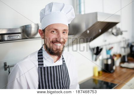Baker in chef hat and apron looking at camera