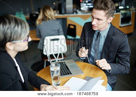 Portrait of young modern businessman talking to woman at table consulting client of banking products