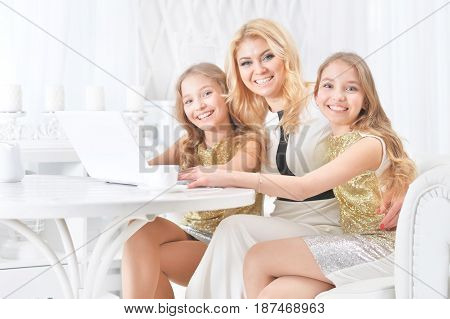 Portrait of a mother with daughters of  twins with a laptop