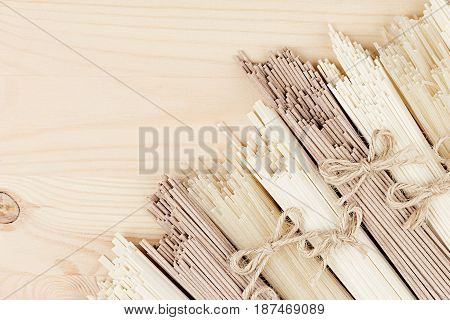 Assortment raw Chinese noodles on soft beige wooden board with copy space top view.
