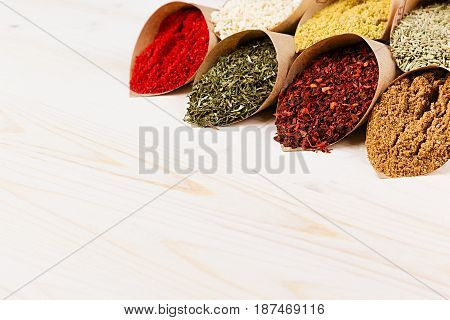 Various colorful powder seasoning close-up in paper corners on white wooden board with copy space.