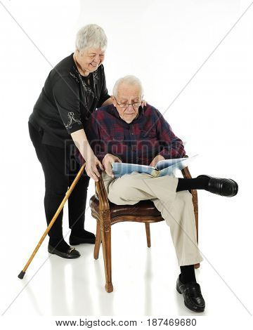 An elderly man looking through a personal book, his wife smiling over his shoulder.  On a white background.