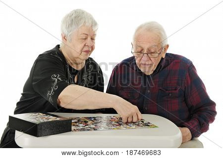 An elderly couple working on a jigsaw puzzle. The man watches as his wife puts in the last piece.  On a white background.