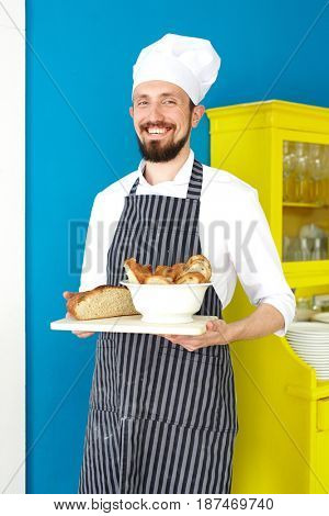 Catering business staff with fresh bread looking at camera