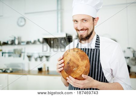 Smiling baker with crusty loaf of bread looking at camera