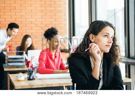 Businesswoman sitting in the office looking up and thinking with pencil at her cheek