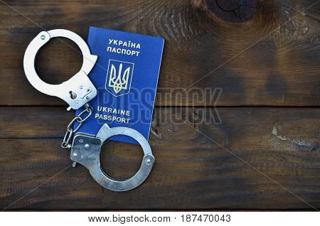 Ukrainian Passport With Police Handcuffs Lies On A Wooden Table. The Concept Of Crime Of Ukrainian C