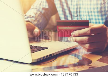 Young businessman holding credit card with online shopping or internet banking online.