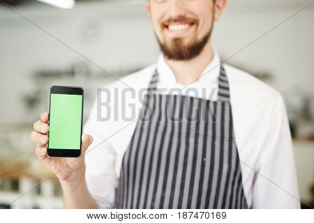 Baker with smartphone showing online video class