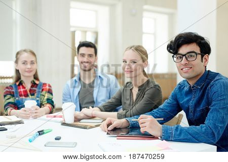 Creative designers sitting by desk and looking at camera
