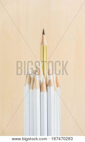 Business concept - lot of white pencils and one color pencil stand on wooden paper background. It's symbol of leadership teamwork united and communication.