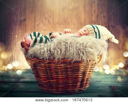 Two weeks old infant baby wearing knitted funny costume sleeping in a basket over wooden background, studio shot. Sweet newborn baby portrait over wood rustic background. New born boy