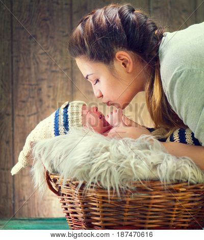 Mother and her Newborn Baby together. Love. Happy Mother and Baby kissing and hugging, posing in studio. Photo of Beautiful Family. Maternity concept. Parenthood. Baby in a basket in cute costume