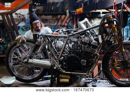 Hipster guy working in custom-bike trouble-shooting center