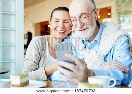Affectionate couple with smartphone having nice leisure in cafe