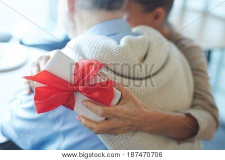 Hand of woman holding gift-box while embracing her husband