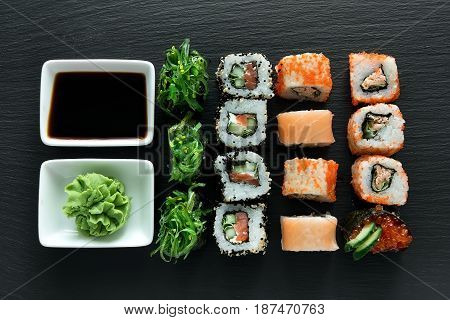 Delicious sushi set with wasabi and soy sauce on a slate table