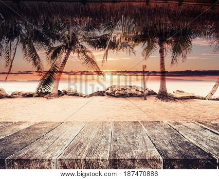 Tropical beach in summer sunset, wood table top with blurred coconut trees, sand and the beach background, vintage tone