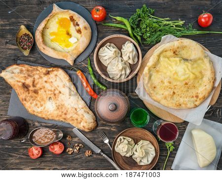 Table and chebureki, khinkali, khachapuri and eastern, tatar cuisine, pepper and spices, topview