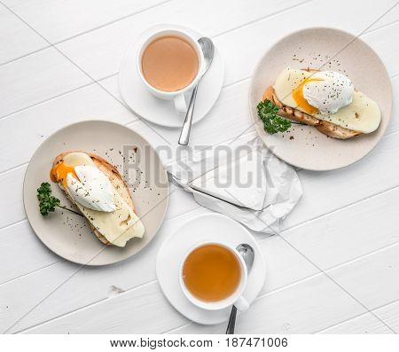 Table served for two, sandwich with poached egg and cups with hot herbal tea, topshot