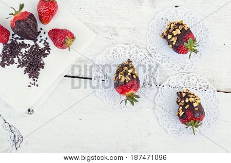 Variety of strawberries covered with a dark chocolate with nuts pistachios on the white wooden table. Homemade choco dipped berry. Gourmet summer dessert. Top view.