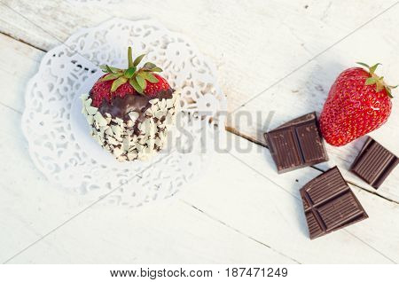Strawberrie covered with a dark chocolate and white chocolate chips on the rustic wooden table. Homemade choco dipped berry. Gourmet summer dessert. Top view.