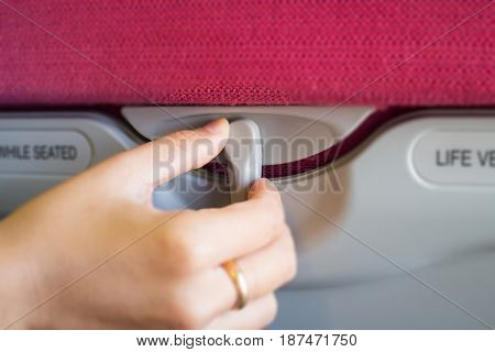 Hand On Hidden Table Of Airplane Seat stock photo