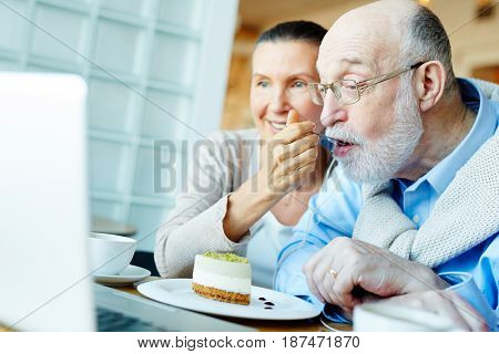 Senior woman feeding her husband while he networking