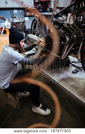 Young biker repairing his custom-bike