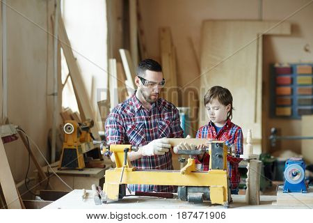 Father and son woodworking in workshop