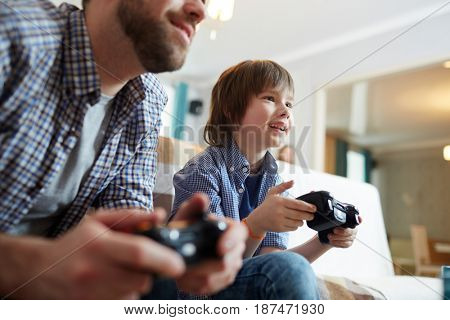 Happy boy with console and his father playing video game at home