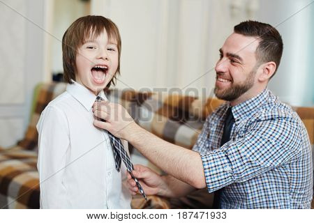 Ecstatic boy looking at camera while his father tying necktie